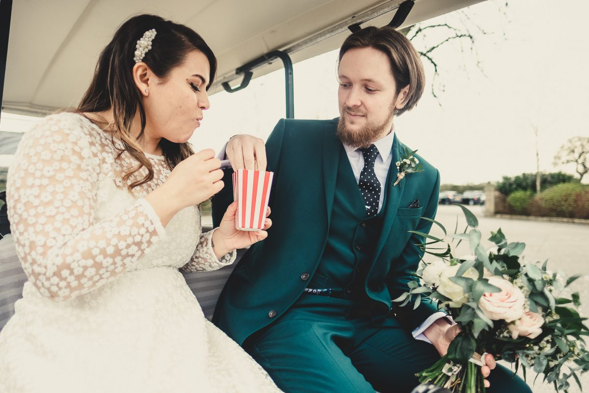 bride and groom eat from a popcorn holder on the back of a golf cart, styal lodge wedding photography, styal lodge wedding photographer, manchester wedding photographer, manchester wedding photography, cheshire wedding photographer, cheshire wedding photography