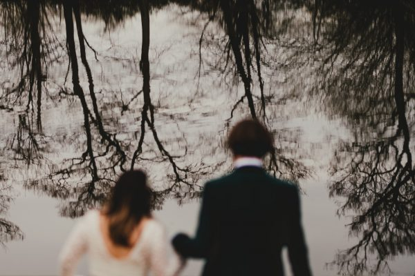 bride and groom walk down to a lake with a reflection of the trees in the water, styal lodge wedding photography, styal lodge wedding photographer, manchester wedding photographer, manchester wedding photography, cheshire wedding photographer, cheshire wedding photography