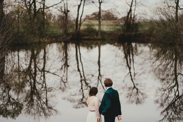 bride and groom look on the lake with a reflection of the trees on the water, styal lodge wedding photography, styal lodge wedding photographer, manchester wedding photographer, manchester wedding photography, cheshire wedding photographer, cheshire wedding photography