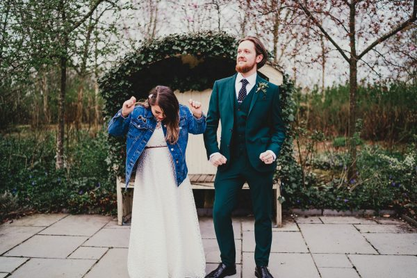 bride and groom have a dance in a garden and bride wears a blue denim jacket over her white dress, styal lodge wedding photography, styal lodge wedding photographer, manchester wedding photographer, manchester wedding photography, cheshire wedding photographer, cheshire wedding photography