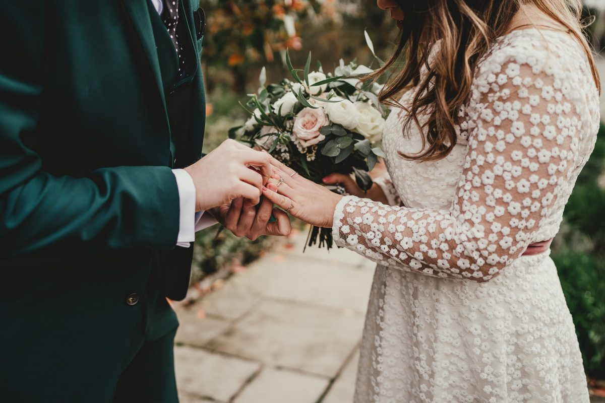 groom puts a ring on his brides finger as she holds her bouquet of flowers, styal lodge wedding photography, styal lodge wedding photographer, manchester wedding photographer, manchester wedding photography, cheshire wedding photographer, cheshire wedding photography