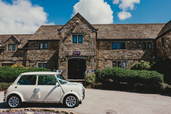 a vintage white mini parked outside a hotel on a wedding day