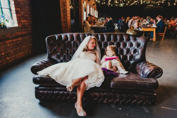 bride sits on sofa with a little girl as they look and smile at each other, elsecar heritage centre wedding photographer, elsecar heritage centre wedding photography, elsecar heritage centre wedding, ayesha photographer, manchester wedding photographer, manchester wedding photography, sheffield wedding photographer, sheffield wedding photography, barnsley wedding photographer, innercity weddings