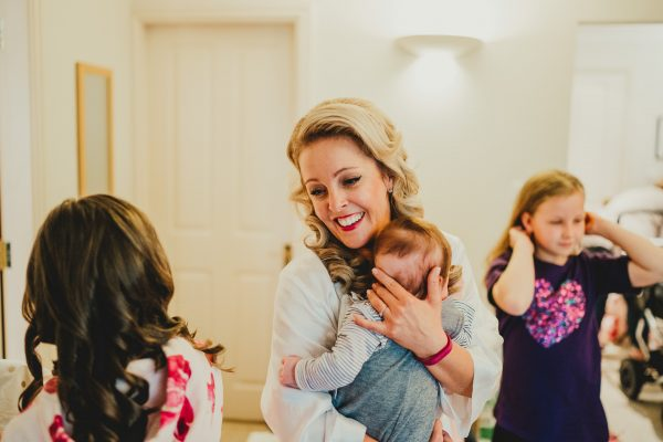 bride holds a baby and smiles at another girl