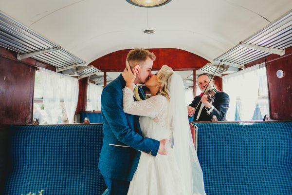 bride and groom kiss on the train with the violinist in the background, elsecar heritage centre wedding photographer, elsecar heritage centre wedding photography, elsecar heritage centre wedding, ayesha photographer, manchester wedding photographer, manchester wedding photography, sheffield wedding photographer, sheffield wedding photography, barnsley wedding photographer, innercity weddings