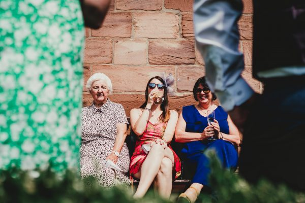 wedding guests sit on bench in the sunshine outside chetham's library, chetham's library wedding photographer, chetham's library wedding photography, lock 91 wedding photographer, lock 91 wedding photography, manchester wedding photographer, manchester wedding photography, cool manchester wedding, creative manchester wedding photographer