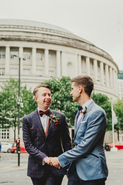 two grooms hold hands and look at each other in front of manchester's central library, chethams library wedding photographer, chethams library wedding photography, manchester wedding photographer, manchester wedding photography, manchester city centre wedding photographer, same sex wedding manchester, ayesha photography, creative manchester wedding photographer, stylish wedding photographer manchester, fun wedding photographer manchester