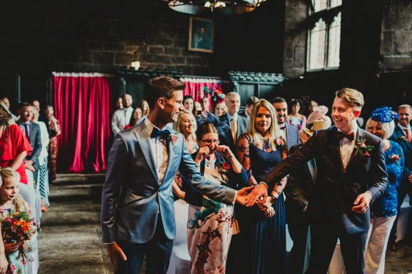 two grooms hold hands at the top of the aisle with wedding guests seated behind them, chethams library wedding photographer, chethams library wedding photography, manchester wedding photographer, manchester wedding photography, manchester city centre wedding photographer, same sex wedding manchester, ayesha photography, creative manchester wedding photographer, stylish wedding photographer manchester, fun wedding photographer manchester