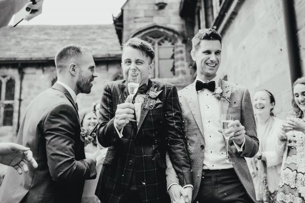two grooms walk through a human confetti tunnel whilst holding their drinks. chethams library wedding photographer, chethams library wedding photography, manchester wedding photographer, manchester wedding photography, manchester city centre wedding photographer, same sex wedding manchester, ayesha photography, creative manchester wedding photographer, stylish wedding photographer manchester, fun wedding photographer manchester