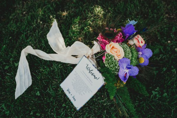 brightly coloured wedding bouquet and wedding invite on the grass, borgo tre rose montepulciano wedding, montepulciano wedding photographer, montepuliciano wedding photography, italy wedding photographer, italy wedding photography, lake como wedding photography, lake como wedding photography, ayesha photography, destination wedding photographer, destination wedding, manchester wedding photographer, manchester wedding photography, uk wedding photography,