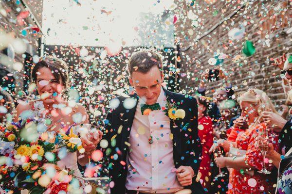 bride and groom walk through a colourful wedding confetti exit, loft studios wedding, loft studios wedding photography, loft studios wedding photographer, loft studios london, london wedding photographer, london wedding photography, urban london wedding, manchester wedding photographer, ayesha photography, humanist wedding in london, colourful wedding,