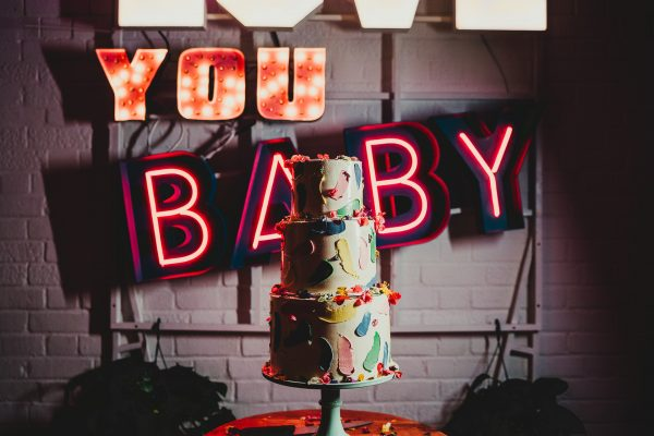 birghtly coloured cake in front of a neon saying love to love you baby, loft studios wedding, loft studios wedding photography, loft studios wedding photographer, loft studios london, london wedding photographer, london wedding photography, urban london wedding, manchester wedding photographer, ayesha photography, humanist wedding in london, colourful wedding,