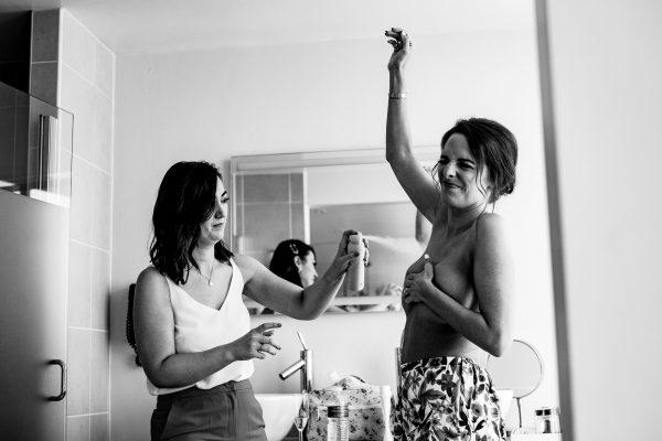 bridesmaid sprays deodorant under brides armpit whilst bride holds herself, loft studios wedding, loft studios wedding photography, loft studios wedding photographer, loft studios london, london wedding photographer, london wedding photography, urban london wedding, manchester wedding photographer, ayesha photography, humanist wedding in london, colourful wedding,