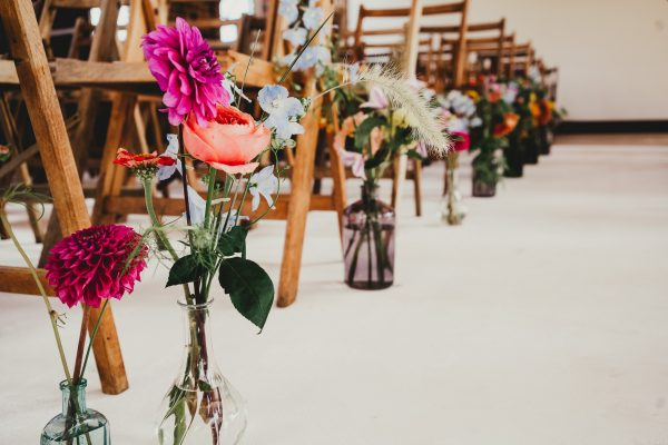 wedding flowers in vases next to ceremony chairs, loft studios wedding, loft studios wedding photography, loft studios wedding photographer, loft studios london, london wedding photographer, london wedding photography, urban london wedding, manchester wedding photographer, ayesha photography, humanist wedding in london, colourful wedding,