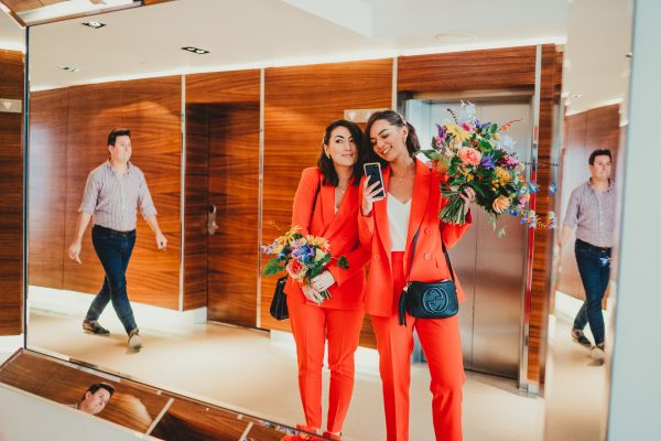 bridesmaids in orange trouser suits holding wedding flowers take a selfie in a mirror, loft studios wedding, loft studios wedding photography, loft studios wedding photographer, loft studios london, london wedding photographer, london wedding photography, urban london wedding, manchester wedding photographer, ayesha photography, humanist wedding in london, colourful wedding,