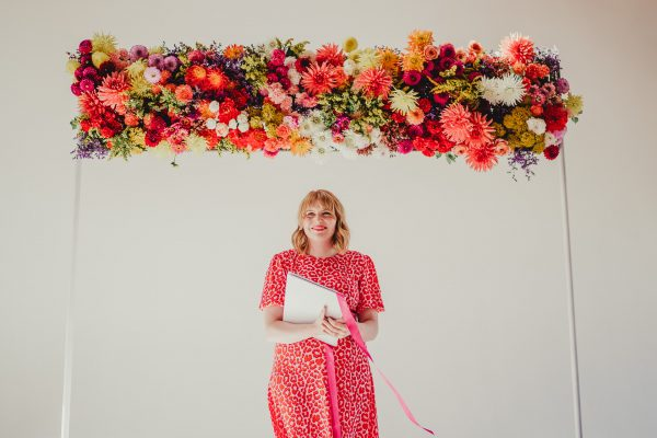 wedding celebrant stands under colourful floral wedding arch, loft studios wedding, loft studios wedding photography, loft studios wedding photographer, loft studios london, london wedding photographer, london wedding photography, urban london wedding, manchester wedding photographer, ayesha photography, humanist wedding in london, colourful wedding,