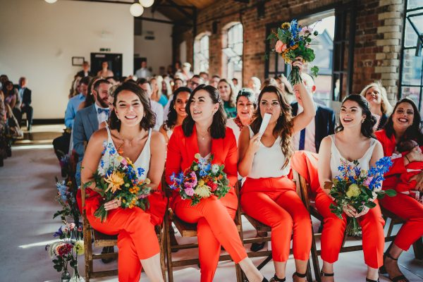 bridesmaids in brightly coloured orange trouser suits sat down in ceremony room whilst holding wedding flowers, loft studios wedding, loft studios wedding photography, loft studios wedding photographer, loft studios london, london wedding photographer, london wedding photography, urban london wedding, manchester wedding photographer, ayesha photography, humanist wedding in london, colourful wedding,