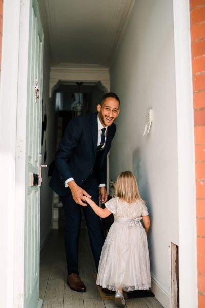 groom opens the front door and holds daughters hand