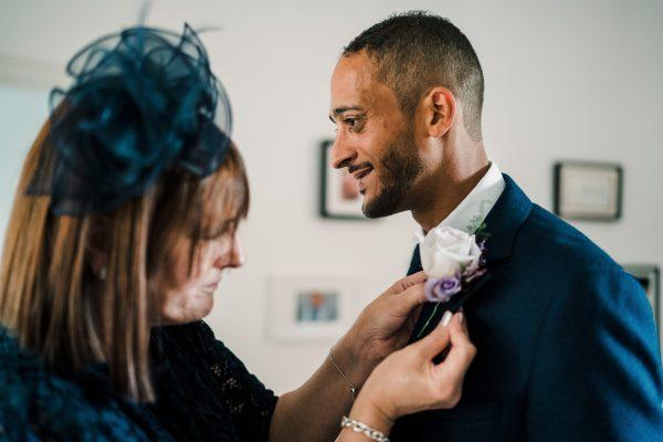 mum pins buttonhole onto the groom