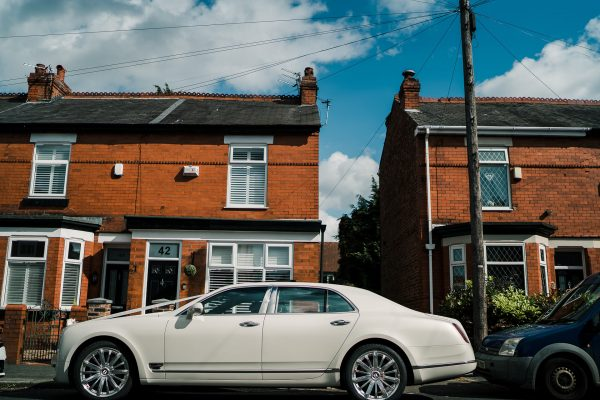 white wedding car outside a house