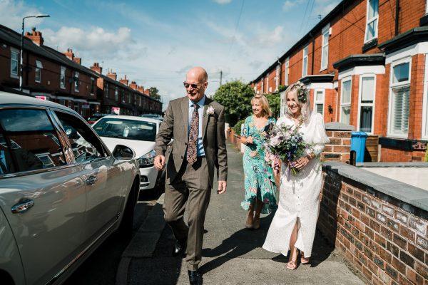 dad, mum and bride walk to the wedding car