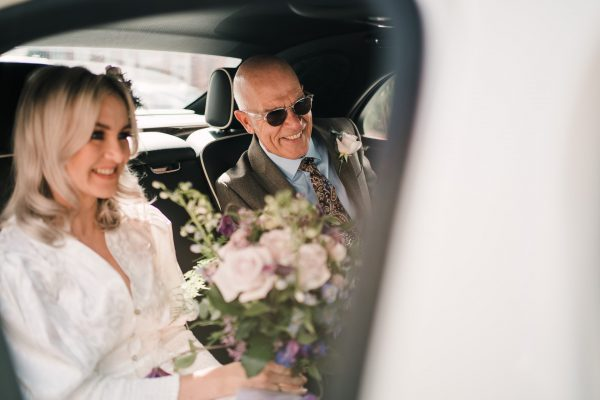 bride holds a bouquet of flowers next to dad in the back of the wedding car