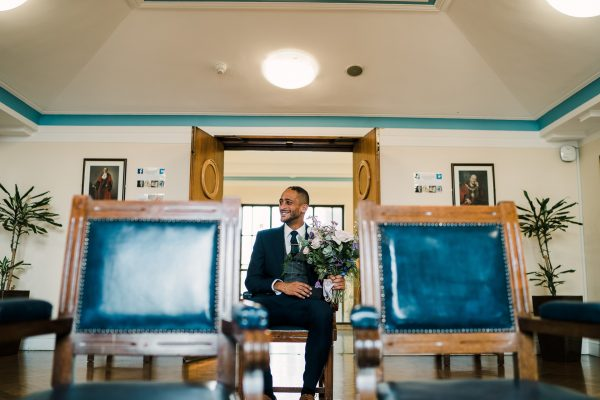 groom holds brides bouquet whilst waiting on his own in the registry office