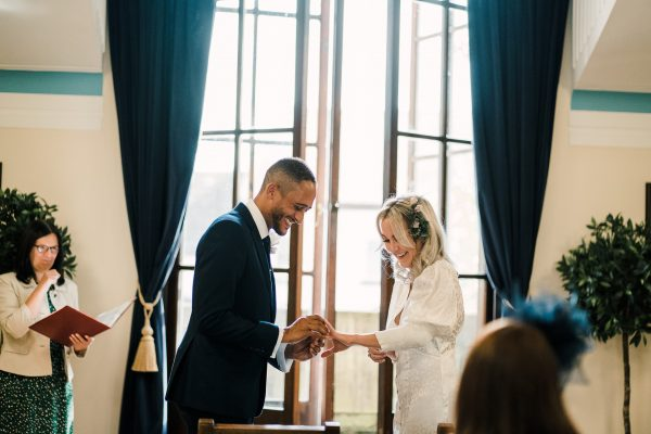 groom places ring on brides finger at sale town hall