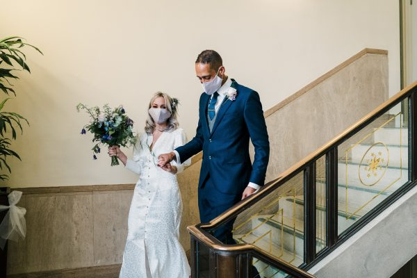 bride and groom leave their covid micro wedding wearing face masks