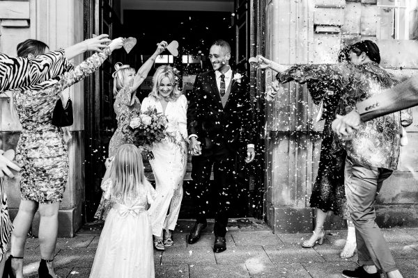 bride and groom exit sale town hall to a tunnel of confetti