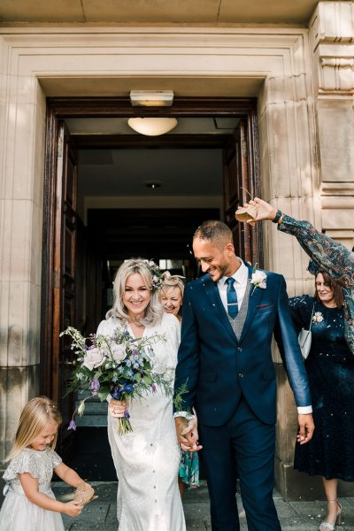 bride and groom outside sale town hall after getting married