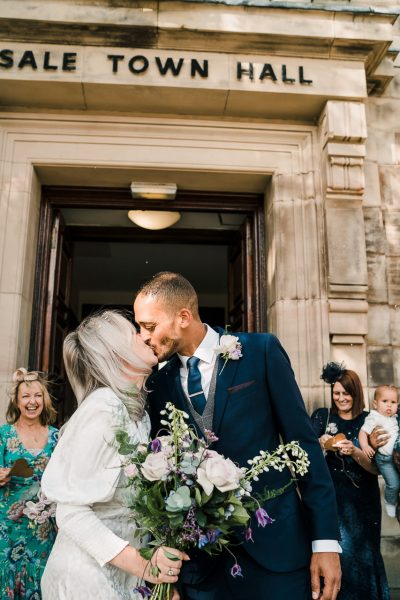 bride and groom kiss outside sale town hall