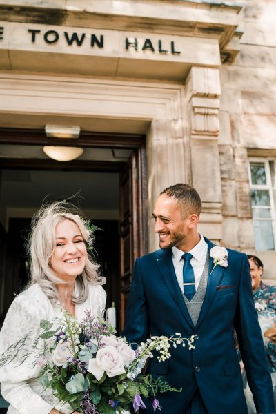 a happy bride and groom outside sale town hall