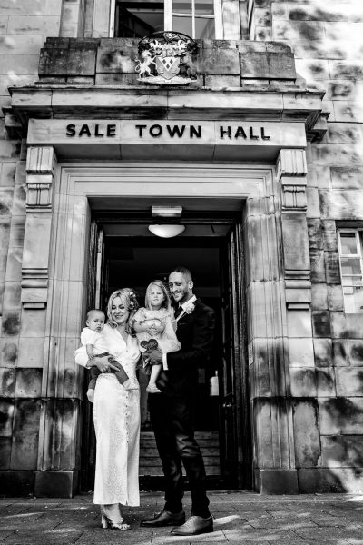 bride holds her son and groom holds their daughter outside sale town hall