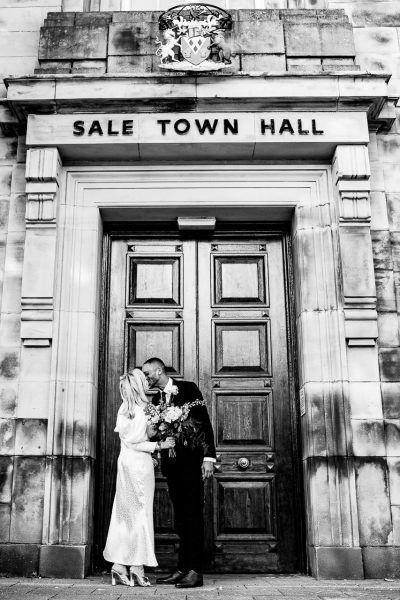 bride and groom kiss outside the doors of sale town hall registry office