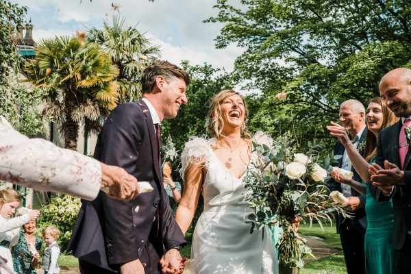 bride and groom exit the Didsbury Parsonage as husband and wife to a tunnel of confetti thrown by their guests