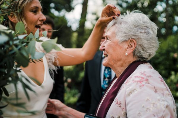 bride picks out confetti from grandmothers hair
