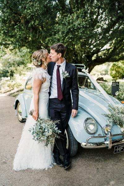 bride and groom kiss whilst leaning on a volkswagen beetle