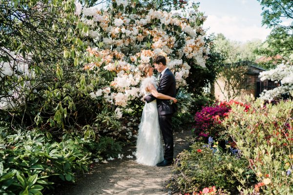 bride and groom cuddle next to pretty blooms