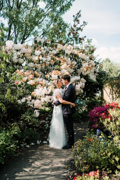 bride and groom kiss next to pretty blooms