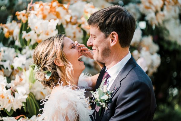 bride throws her head back laughing whilst groom holds her next to pretty blooms
