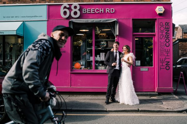 bride and groom stand outside 68 Beech Road in chorlton with champagne as a cyclist rides past