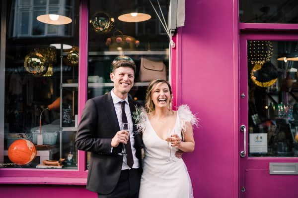 bride and groom laughing whilst holding champagne