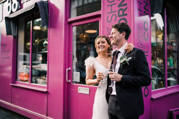 bride wears charlie brear wedding dress, holding a glass of champagne with the husband who wears a plum suit