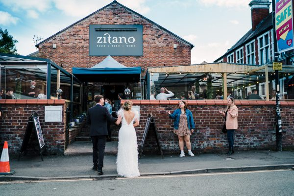 bride and groom enter Zitano in Chorlton for their wedding reception with onlookers wishing them well