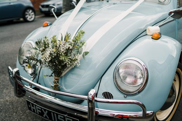 pale blue volkswagen beetle dressed with flowers and ribbons for a wedding