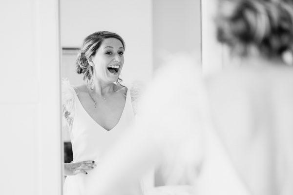 bride sees herself in the mirror wearing her wedding dress