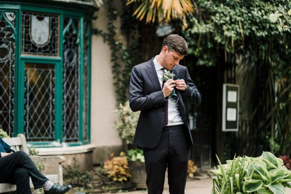 groom stands outside the Didsbury Parsonage before getting married reattaching his button hole