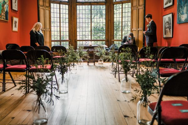 inside the ceremony room at the Didsbury Parsonage dress with flowers along the aisle