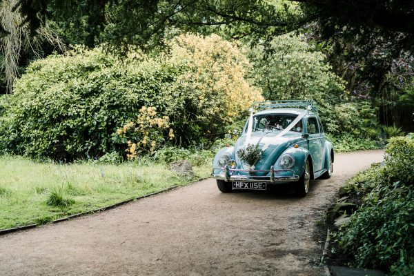 pale blue volkswagen beetle arrives at wedding venue at Didsbury Parsonage